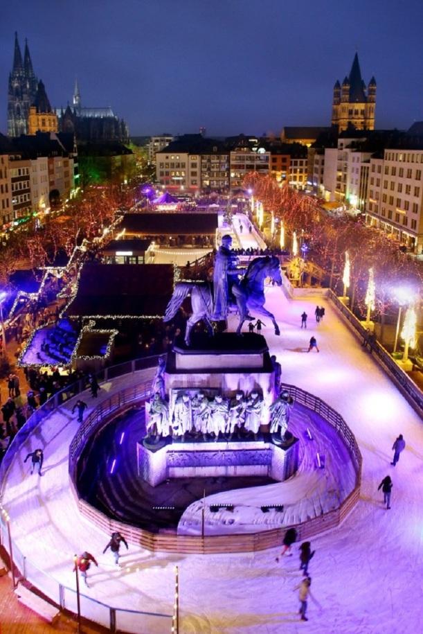"""Blick auf die große Eisbahn auf dem Weihnachtsmarkt """"Heimat der Heinzel"""" auf dem Heumarkt in der Altstadt Köln, im Vordergrund das Reiterdenkmal, im Hintergrund Dom und Groß St. Martin."""
